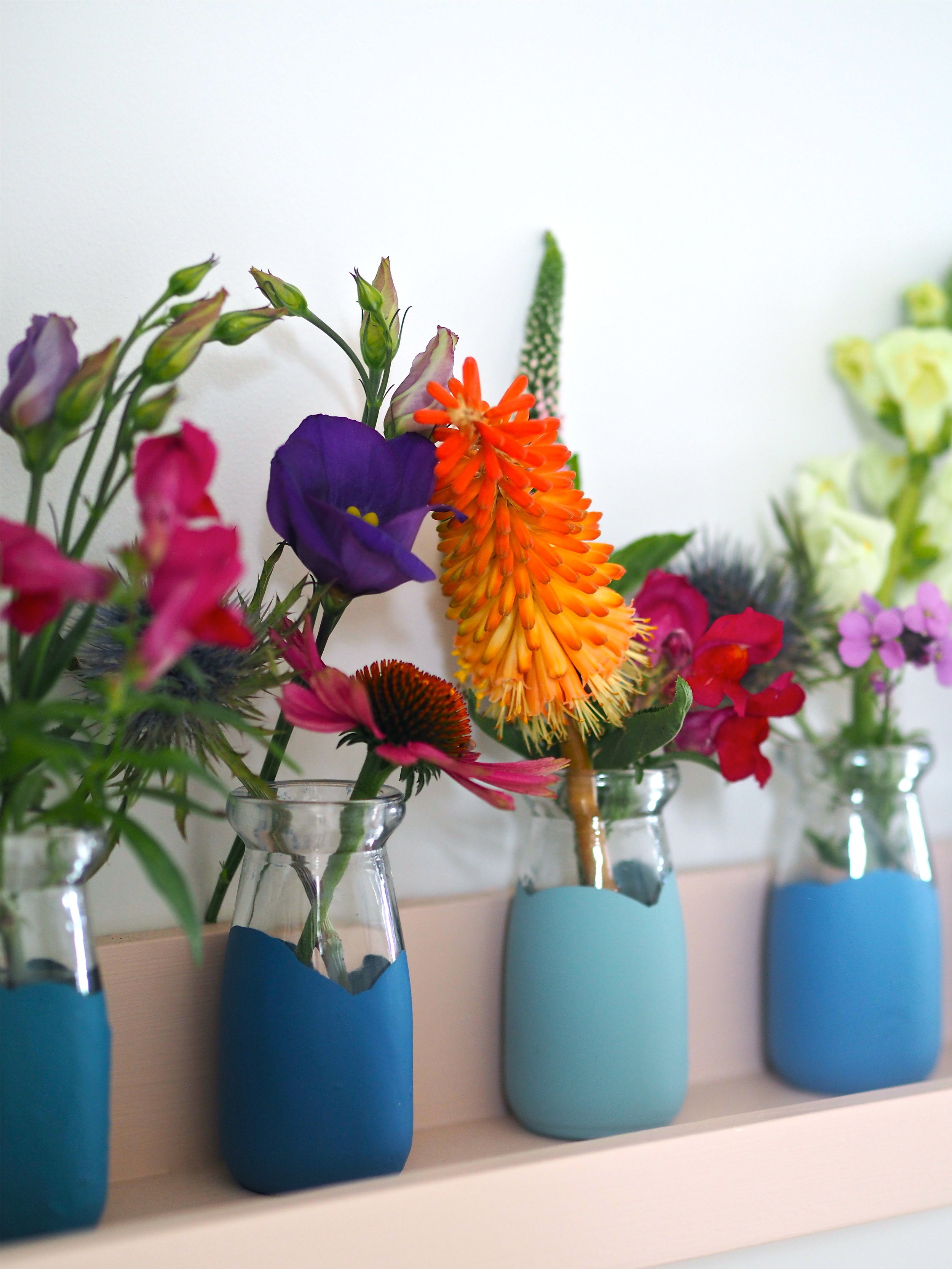 A collection of milk bottles dipped in blue shades by M&L Paints.