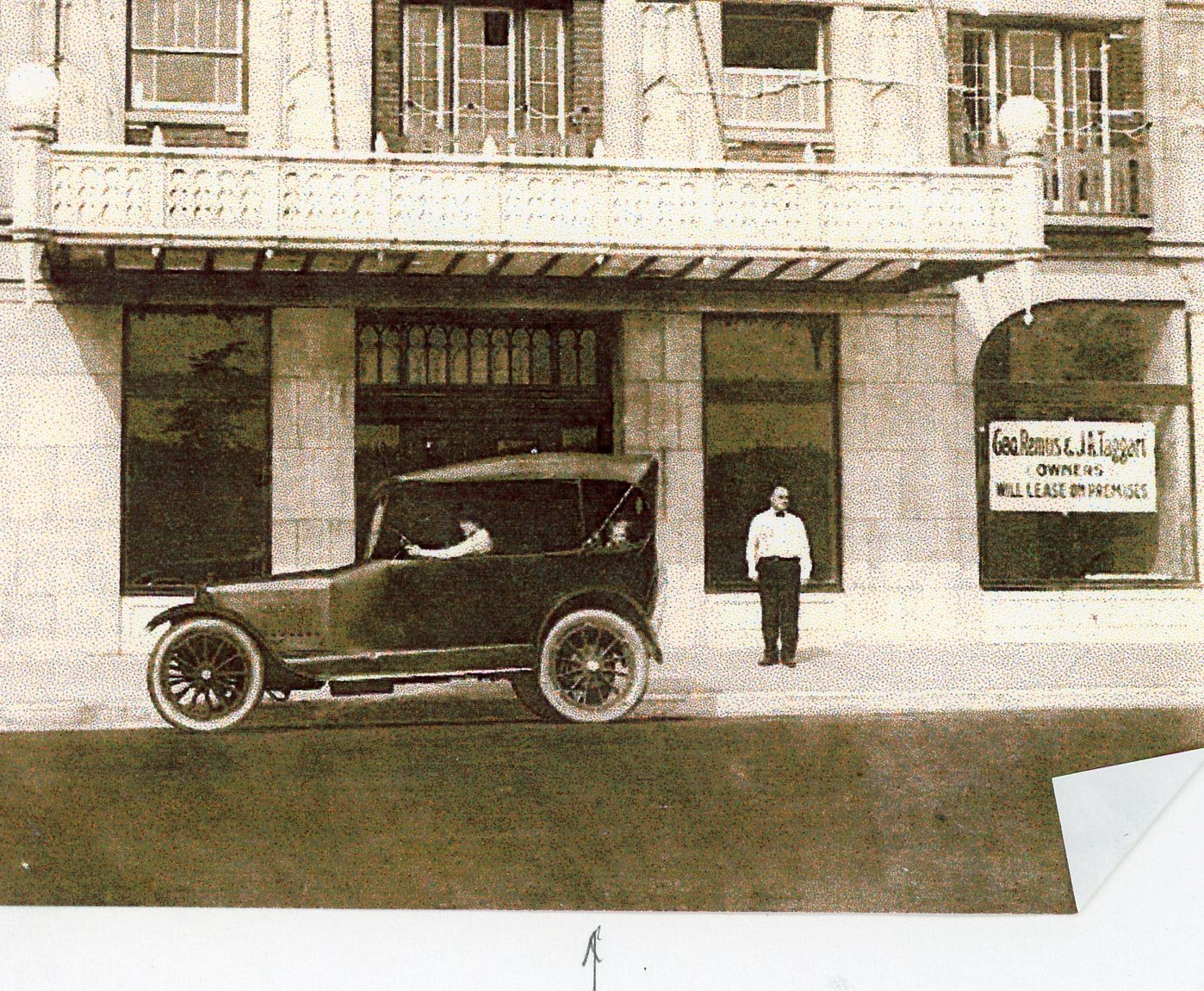 Remus during his pharmacy years, pictured standing in front of the nine-story Geo. Remus and J.A. Taggart Office Building at 4520 North Clarendon Avenue in Chicago, near Lake Shore Drive and on the edge of Buena Park and Uptown. Lillian is in the driver's seat, while Romola is sitting behind her.
