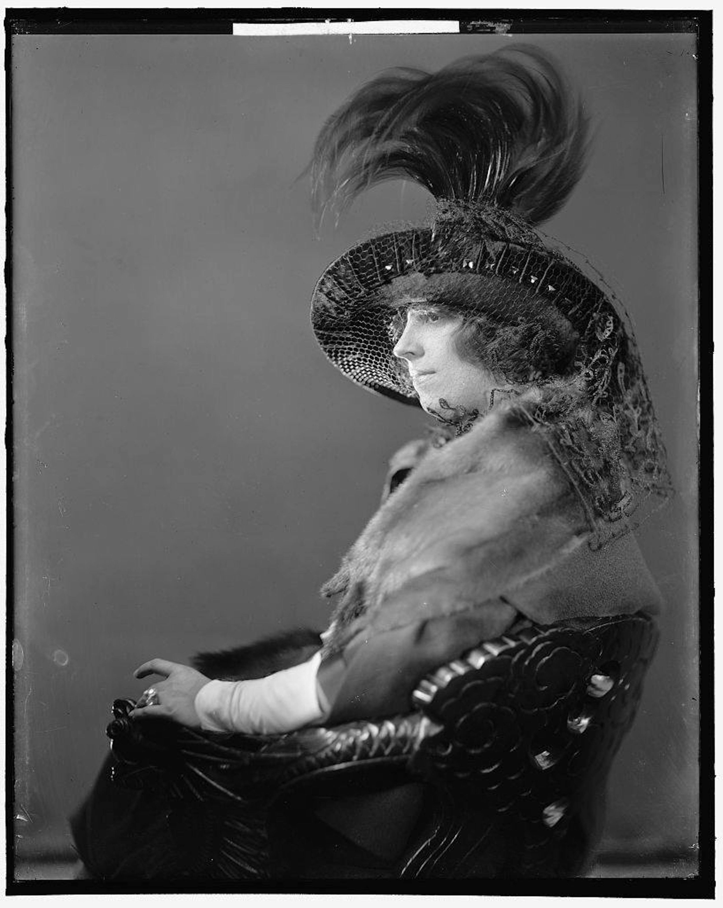 Imogene Remus sits for a formal portrait in her finest fur shawl and feathered hat. Her stunning diamond wedding ring is prominently displayed, which may indicate that this photo was taken shortly after she and George were married in Newport, Kentucky, on June 25, 1920.