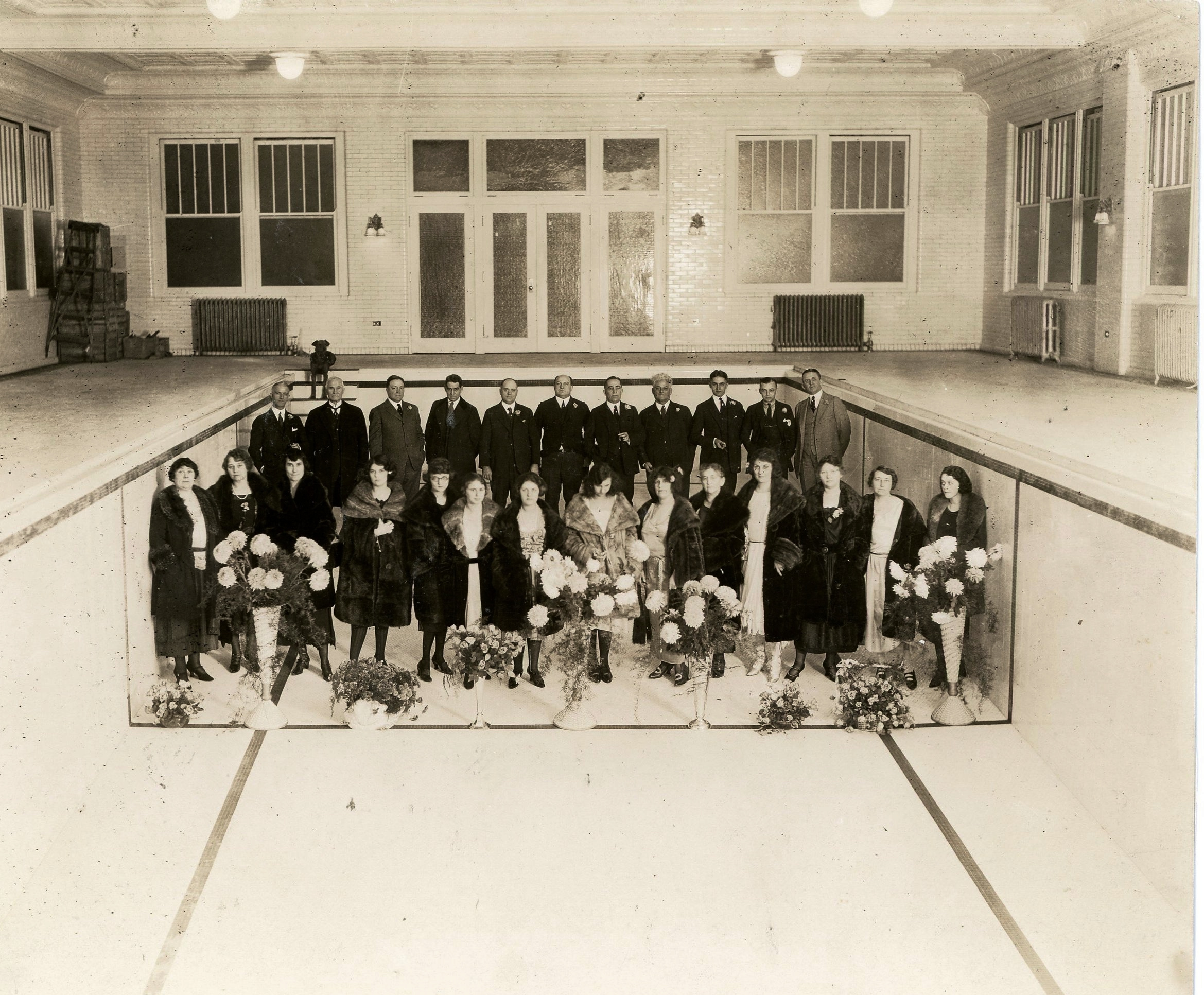 """George, Imogene, and Ruth pose with their guests for a formal portrait inside the famous """"Imogene Baths"""" prior to it opening on December 31, 1921. Reports estimate that Remus paid up to $175,000 for the Grecian swimming pool, lined with tile from Cincinnati's famous  Rookwood Pottery ."""