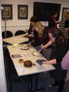 'College Staff sampling and scoring the cakes, and enjoying the difficult task!'