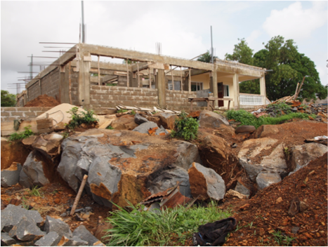 Side-view of the two classrooms & the stones in foreground will form the foundation for the school veranda