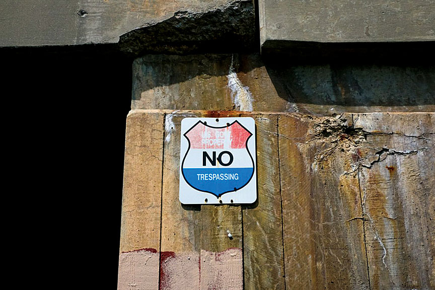 "One of many ""No Trespassing"" signs along the cement overpass walls of U.S. Route 40 in West Baltimore."