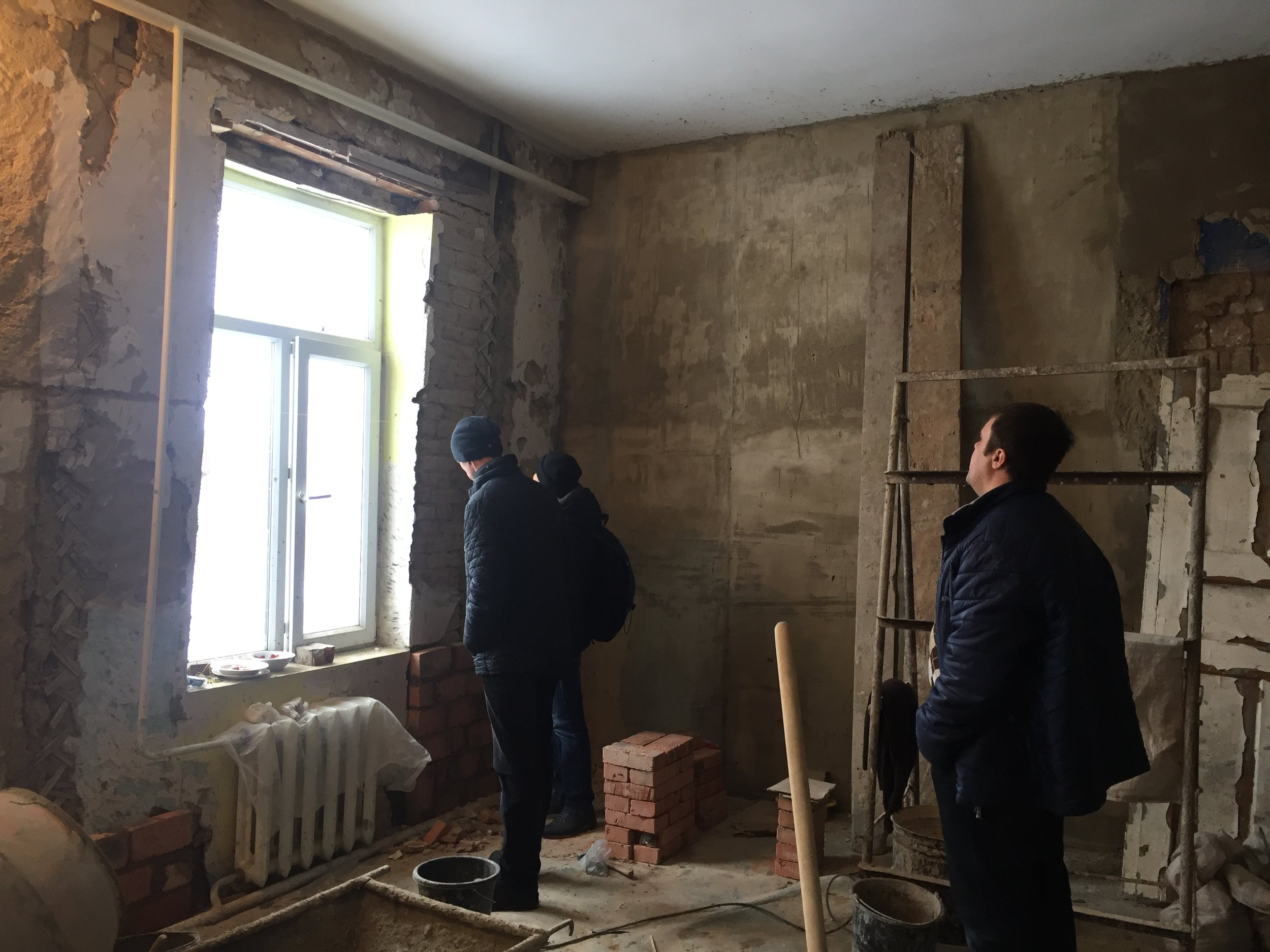 Gert's team working on renovating a third room for the building one inhabitants. Currently, they only have two rooms where they can stay.