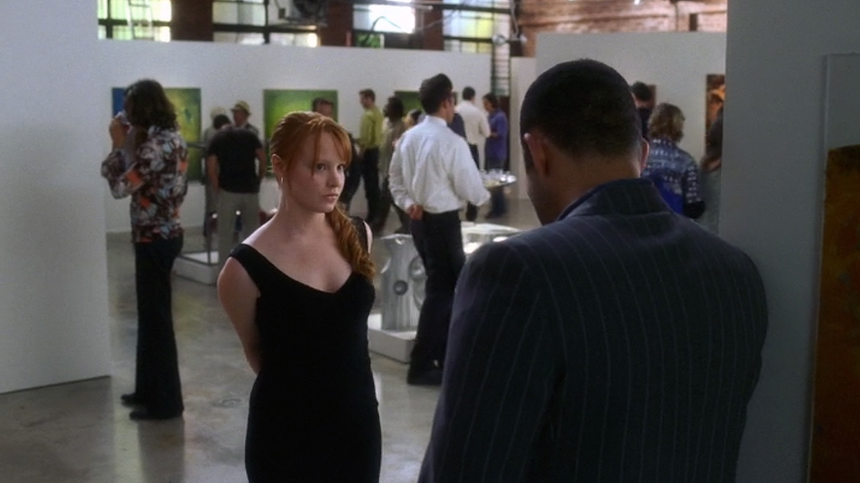 Claire during gallery scene with abstract panels in background