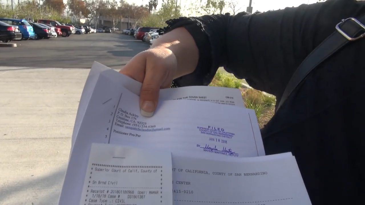 A still image from Todd Standing's YouTube announcement that shows court documents, held by Claudia Ackley, representing the case.
