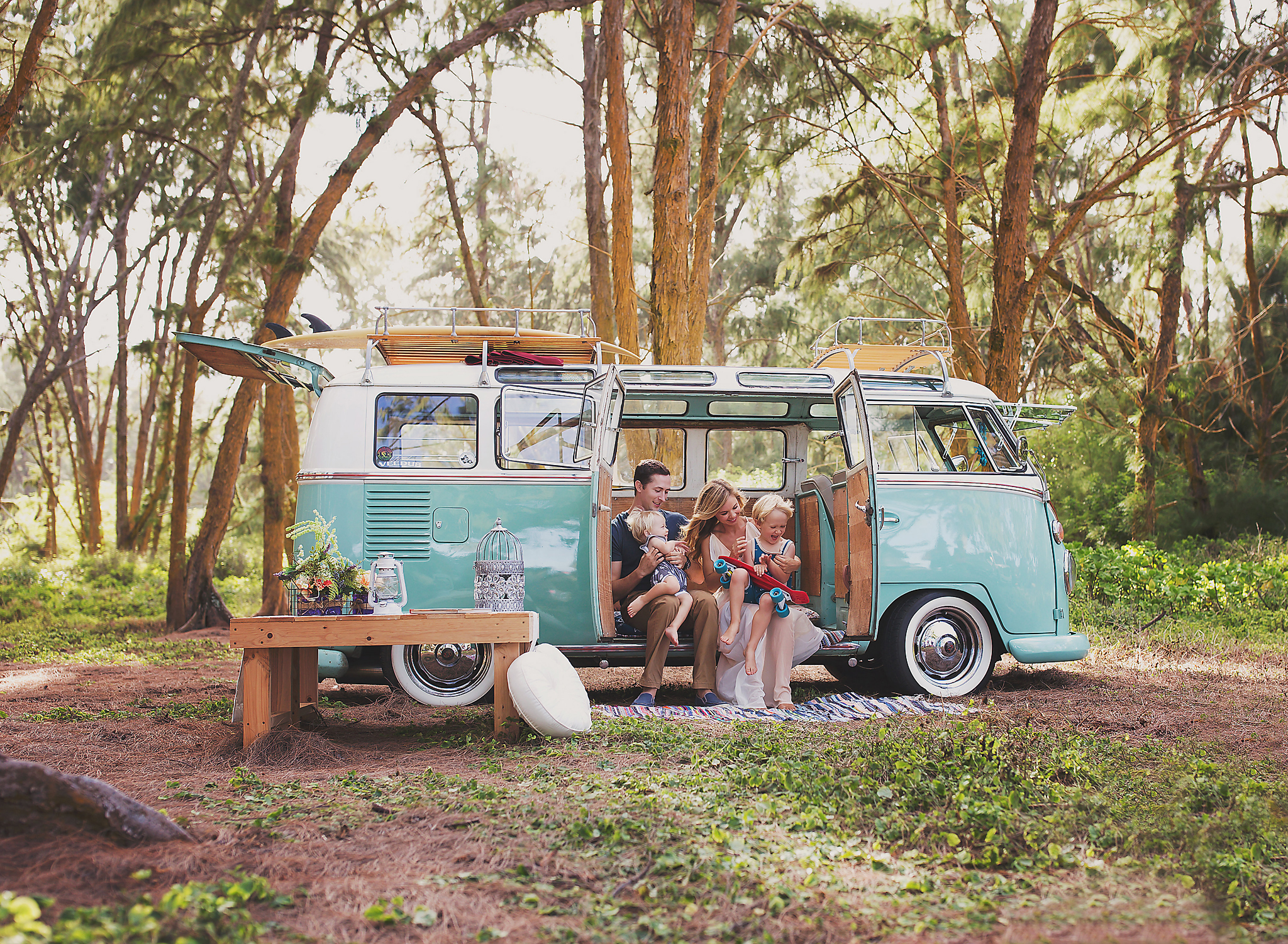 Family of 4 sitting in the open side door of a teal VW Bus parked in a wooded area at Bellows Beach, Wiamanalo, Hawaii.