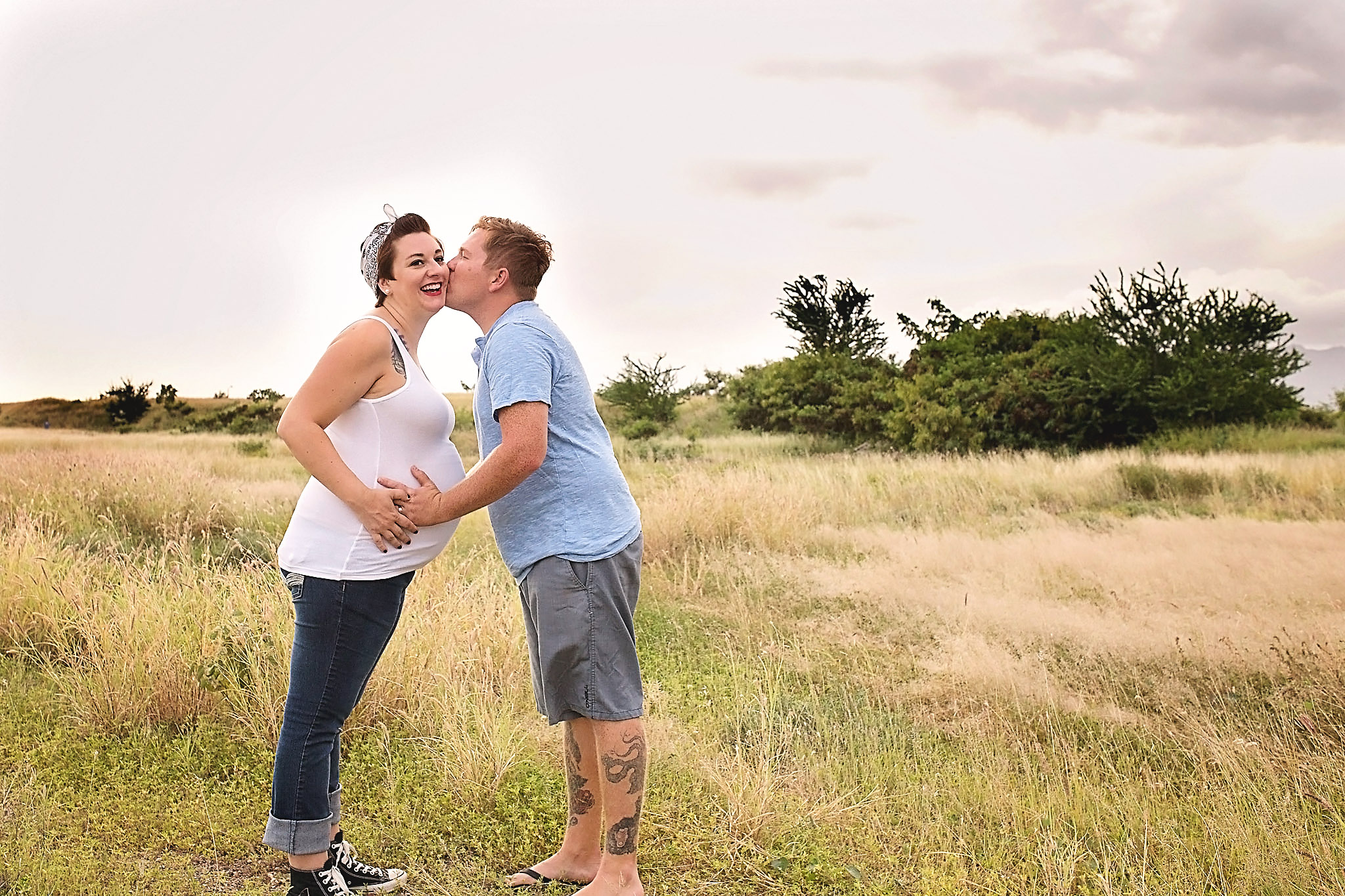 Husband kissing his pregnant wife's cheeck while both have hands placed on her belly.