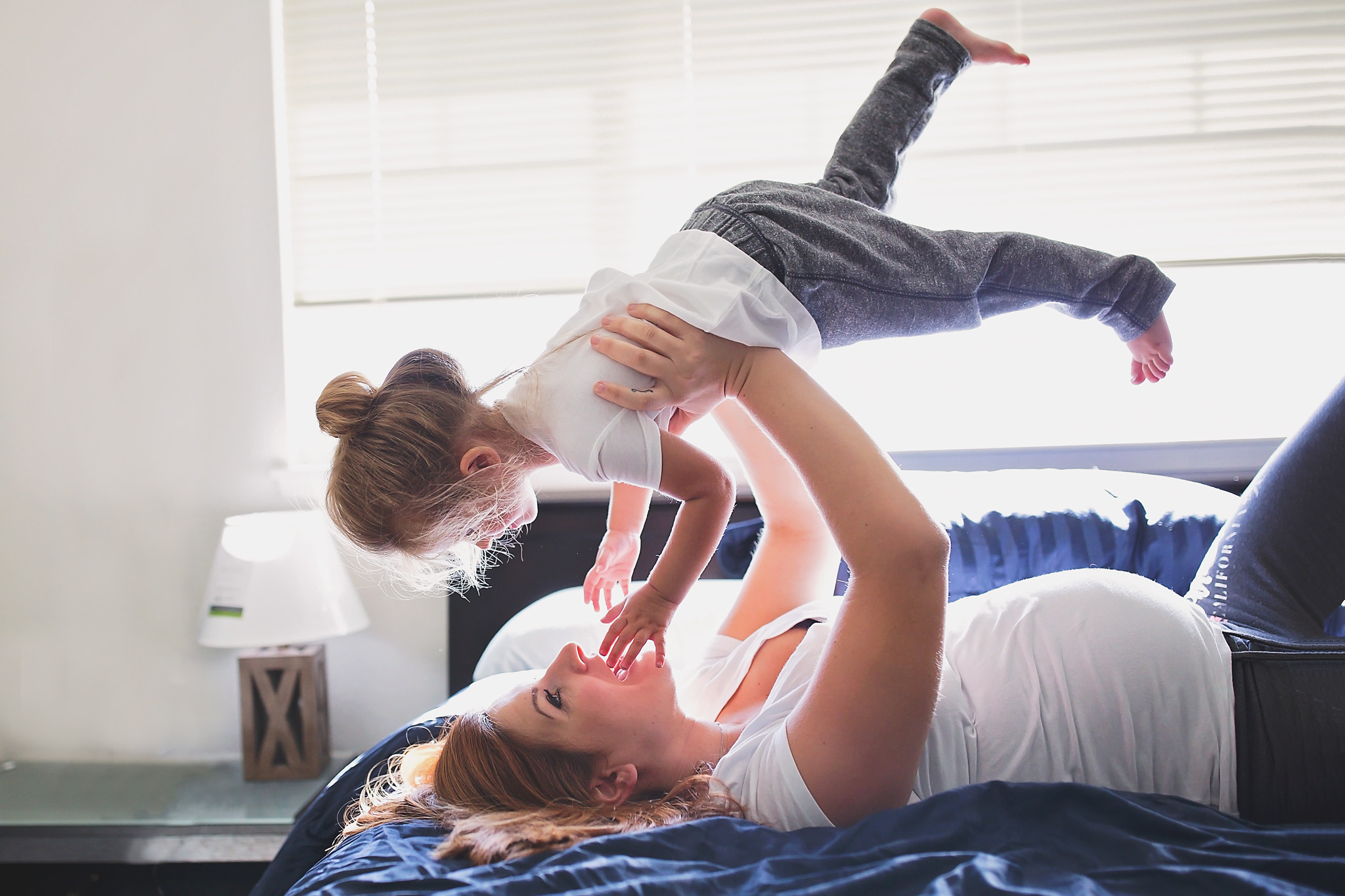 Mother raising toddler up over her head as she lays in bed durning in home maternity session.