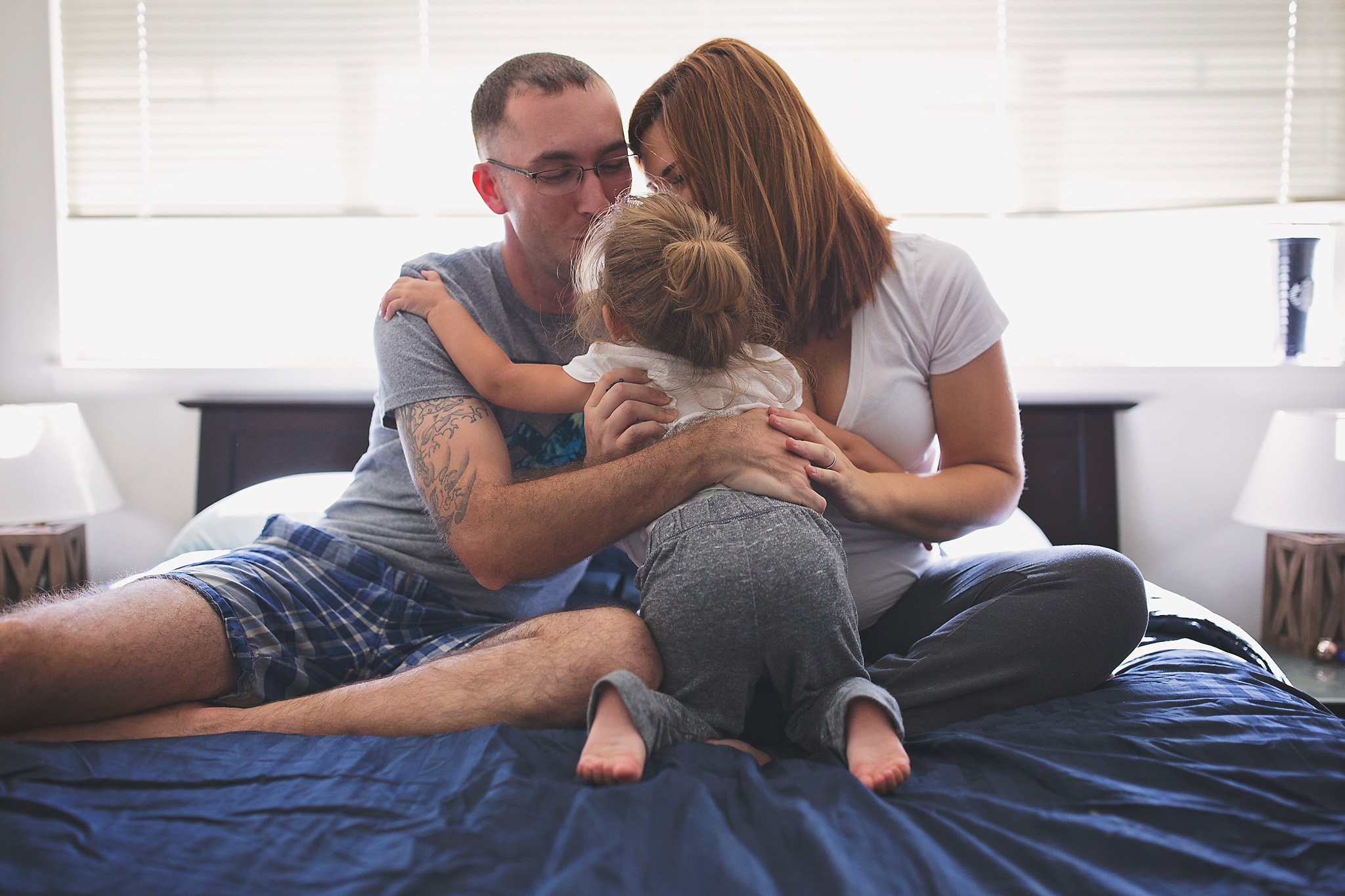 Family of 3 hugging in bed durning in home maternity session.