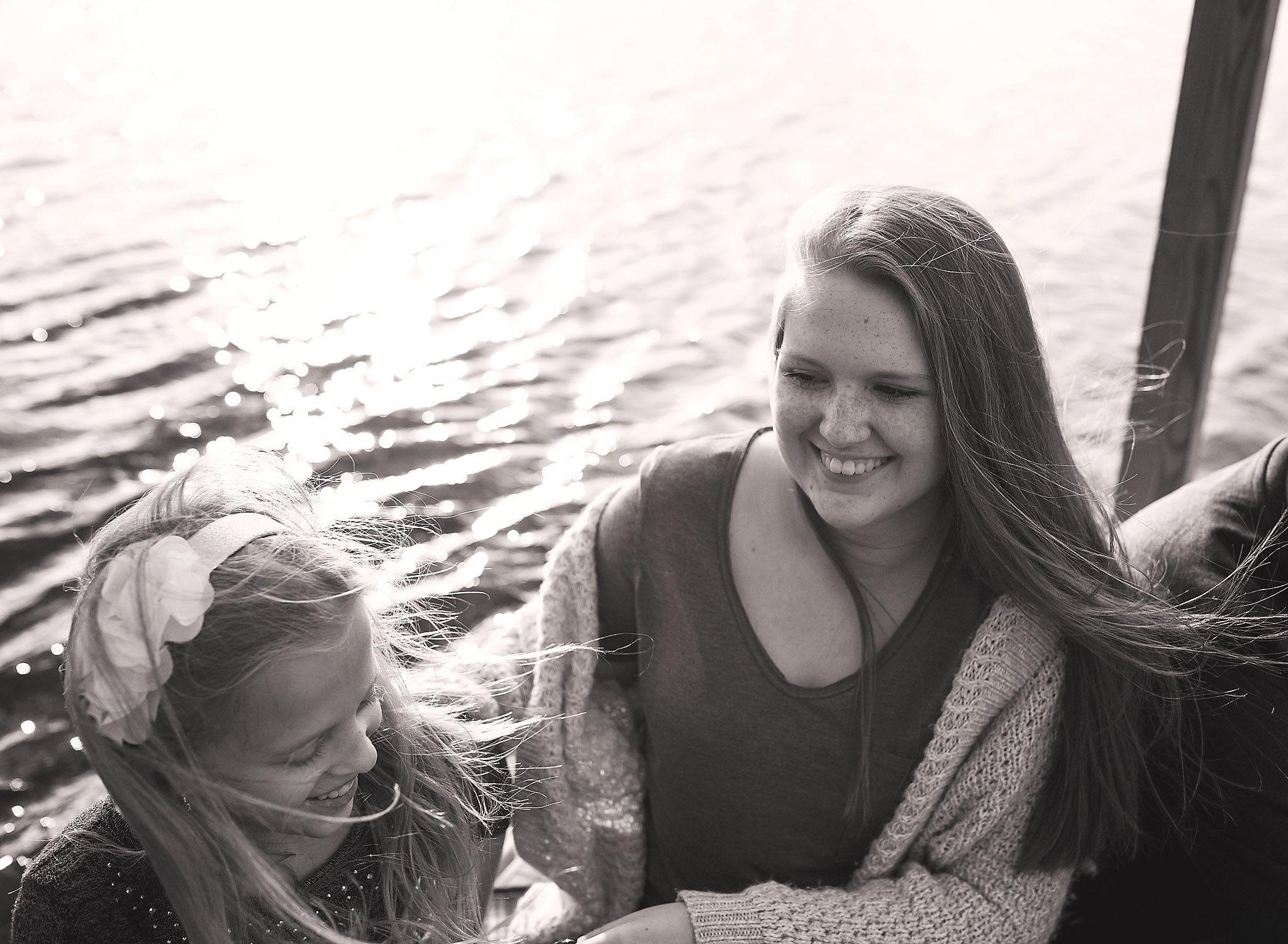 Teenage girl and her younger sister sitting on a dock along the water smiling at each other with their hair gently flowing in the wind.