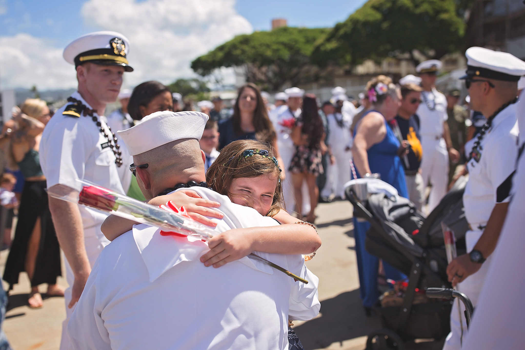 Yougn girl empracing her U.s. Navy salior father with a huge smile on her face at his homecoming