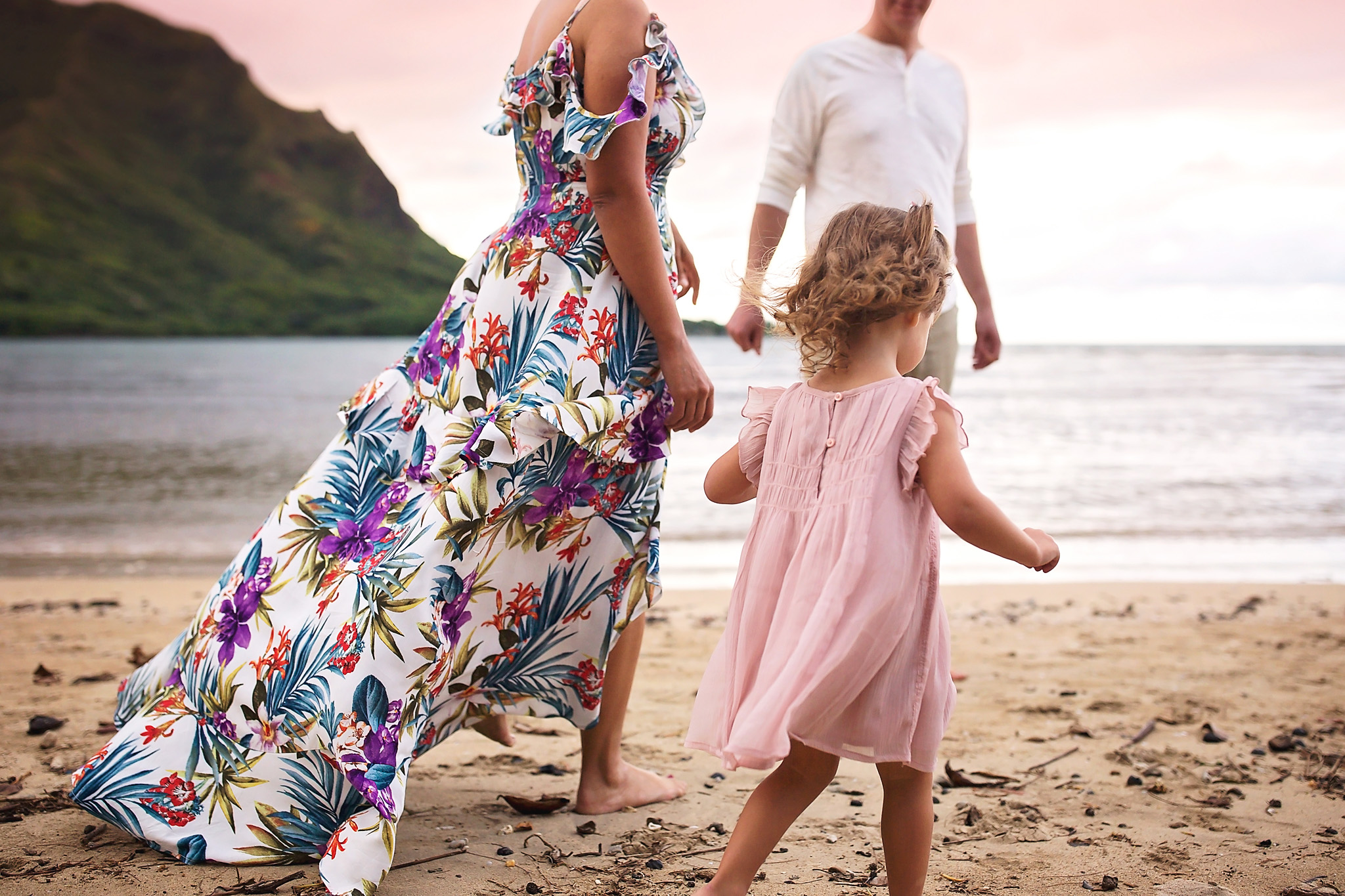 Mother and father standing on the beach looking over at their toddler daughter exploring on the beach in a pink dress.