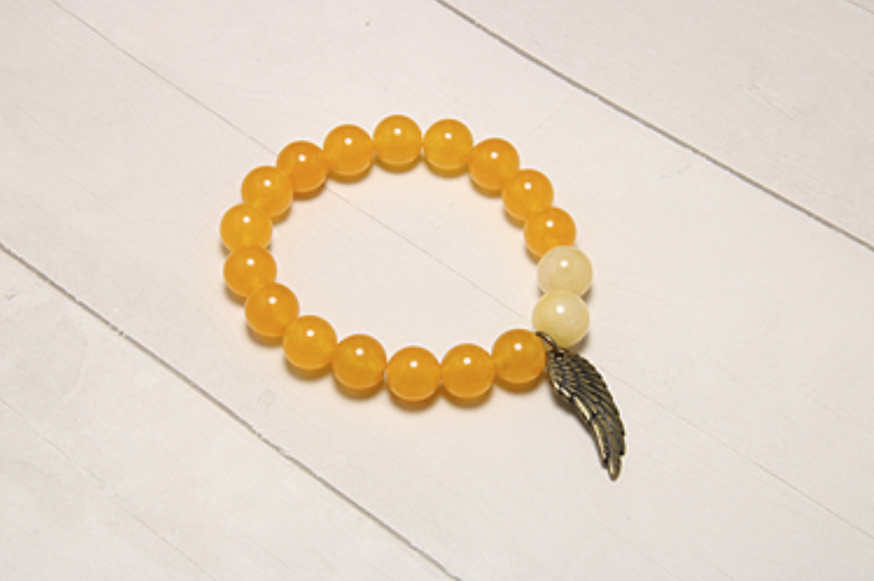 The Agate and Mother of Pearl bracelet features bright orange stones and a cute feather charm. Mother of pearl is meant to shield negativity and offer protection.