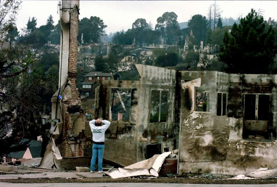 A man looks at a destroyed home on Broadway Terrace in October 1991, after the Oakland hills fire that devastated the area a few days earlier, killing dozens of people.    Photo: Deanne Fitzmaurice / The Chronicle 1991