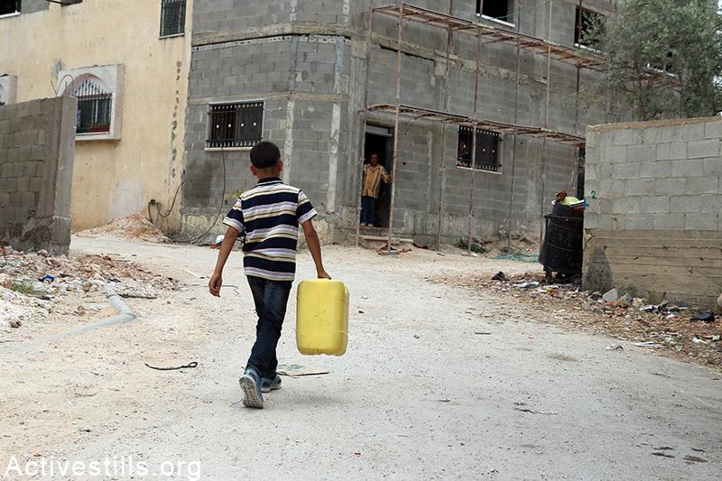 Palestinian child carries water gallon in Qarawat Bani Hassan village, West Bank, May 23, 2015. (photo: Ahmad al-Bazz / Activestills.org)