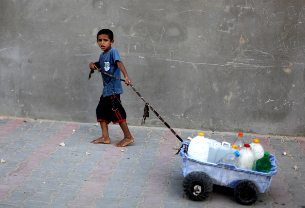 Palestinian child transporting his family's bottles, filled with potable water from a purification station, in Deir al-Balah central Gaza Strip, on May 22, 2013. (Photo: Ashraf Amra/APA Images) -