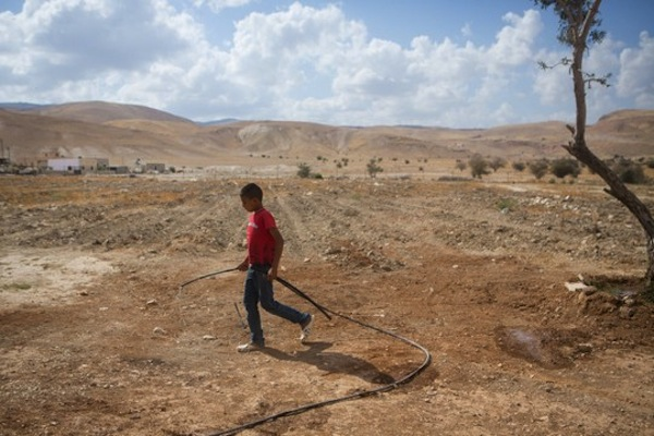 A young Palestinian boy from the West Bank village of Fasayil, Jordan valley, seen walking with a water pipe in the village. May 14, 2015. (Miriam Alster/Flash90)