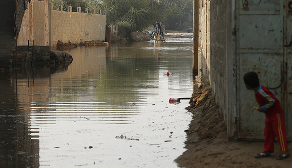 A boy looks at Palestinians as they ride a horse cart on a street flooded with sewage water from a sewage treatment facility in Gaza City, Gaza, Nov. 14, 2013.(photo by REUTERS/Mohammed Salem)