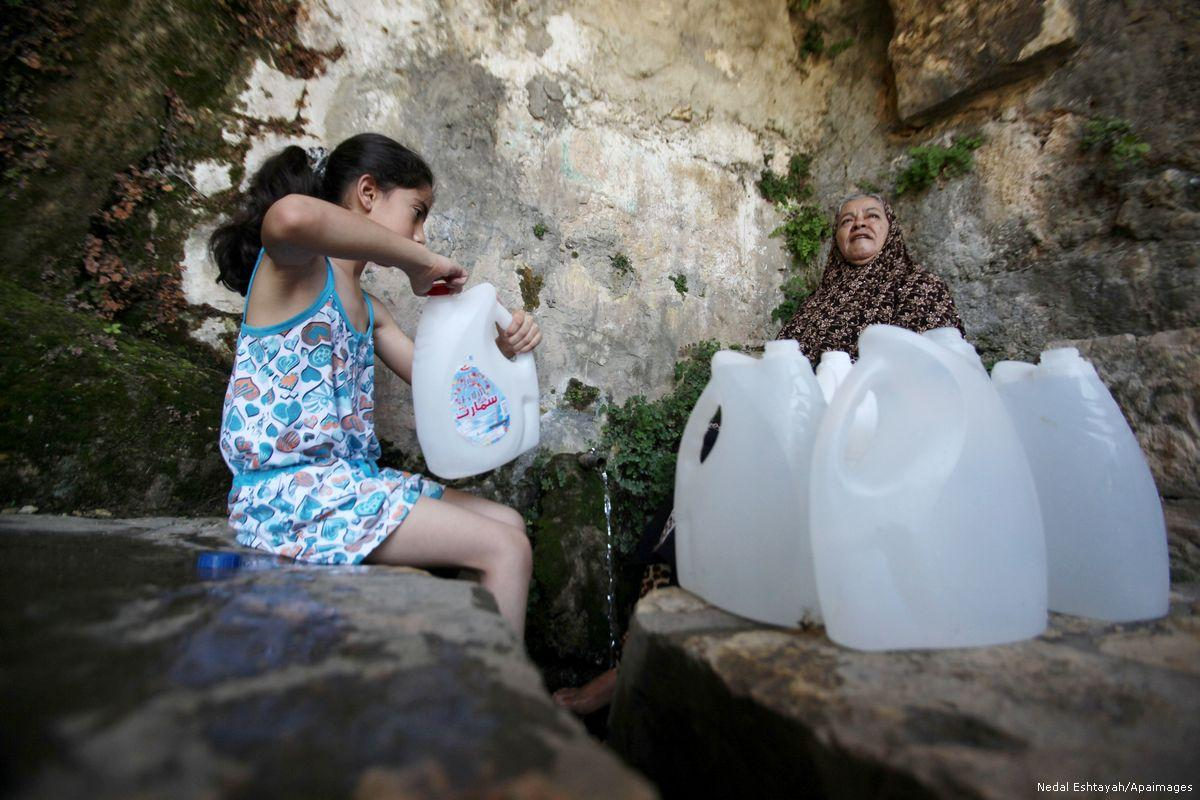 A Palestinian girl fills jerrycans with spring water in Salfit, West Bank on 27 June 2016. (Medal Eshtayah/Apaimages)