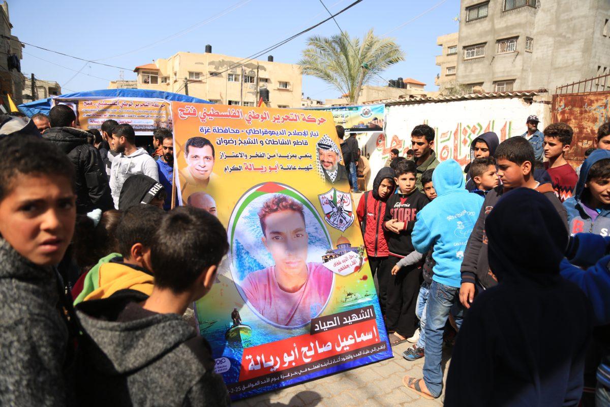 Children crowd around a poster of Ismail Abu Riyala. Photo:Messiah Gadzo