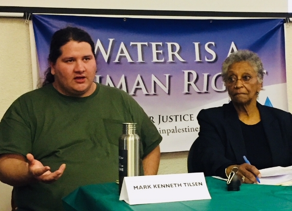 Dorotea Manuela of Boston's Color of Water Project listens as Mark Kenneth Tilsen describes the Lakota struggle to protect water resources.