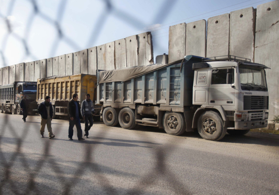 Palestinians walk past trucks loaded with gravel at the Kerem Shalom crossing between Israel and the southern Gaza Strip December 30, 2012.. (photo credit: REUTERS)