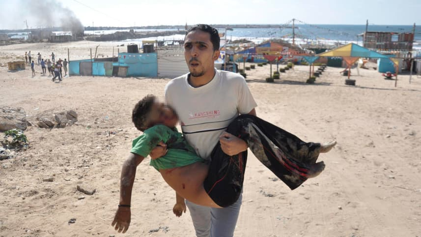 A Palestinian man carries the body of a boy, whom medics said was killed by a shell fired by an Israeli naval gunboat, on a beach in Gaza City July 16, 2014.Reuters