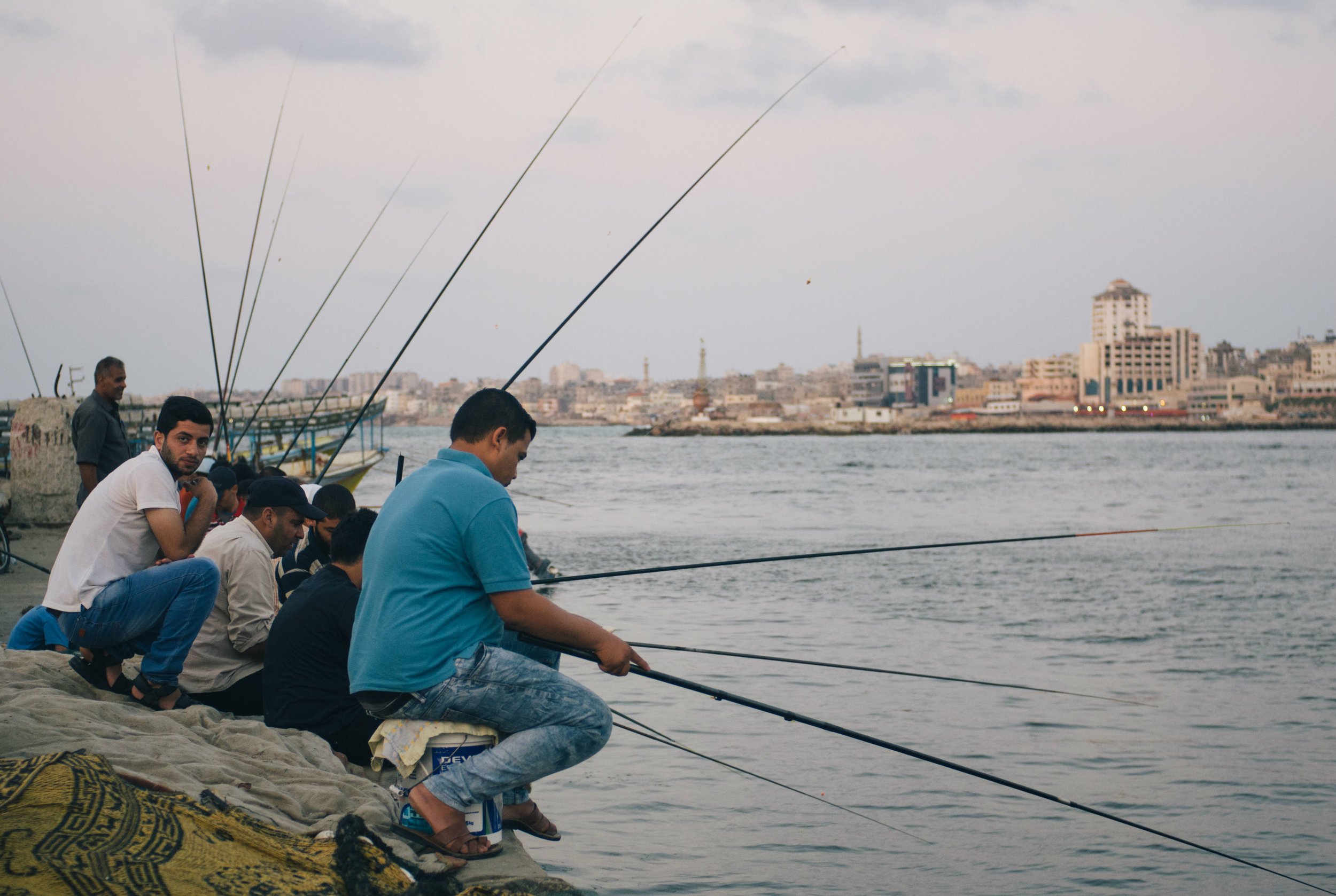 Palestinian men sit together at Gaza's port when they don't have work, which is often for the enclave's many unemployed, drinking coffee as they watch their rods (Kaamil Ahmed/MEE)