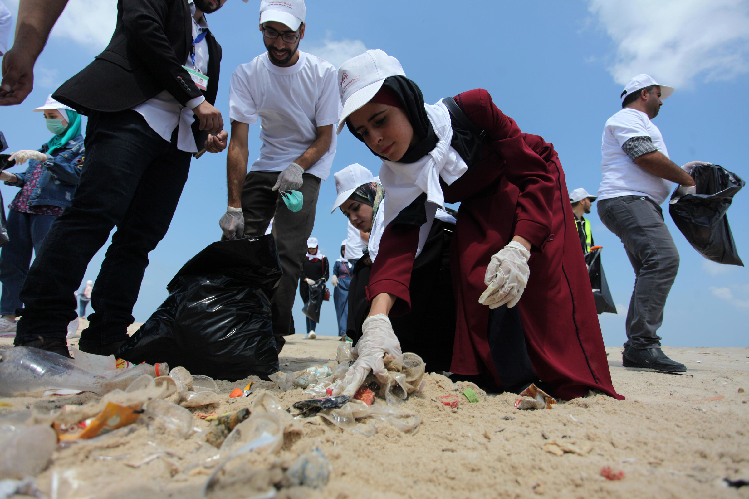 Palestinian youth clean up a Gaza City beach on August 7. Mahmoud Ajjour/APA images