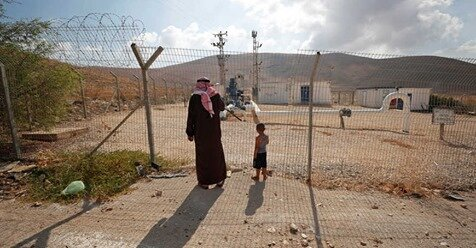 REUTERS/Mohamad Torokman  Palestinians stand by a fence as they look at Israeli water pipes in the Jordan Valley, Israeli-occupied West Bank, Aug. 21, 2019.