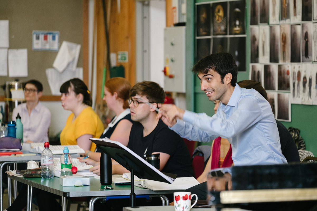 JONATHAN SANTAGADA CONDUCTS THE COMPANY OF TOSCA IN REHEARSAL. PHOTO CREDIT: © TOM ARBER