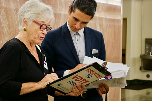LWVDC member Judy Osborne registering new voters after the Naturalization Ceremony.