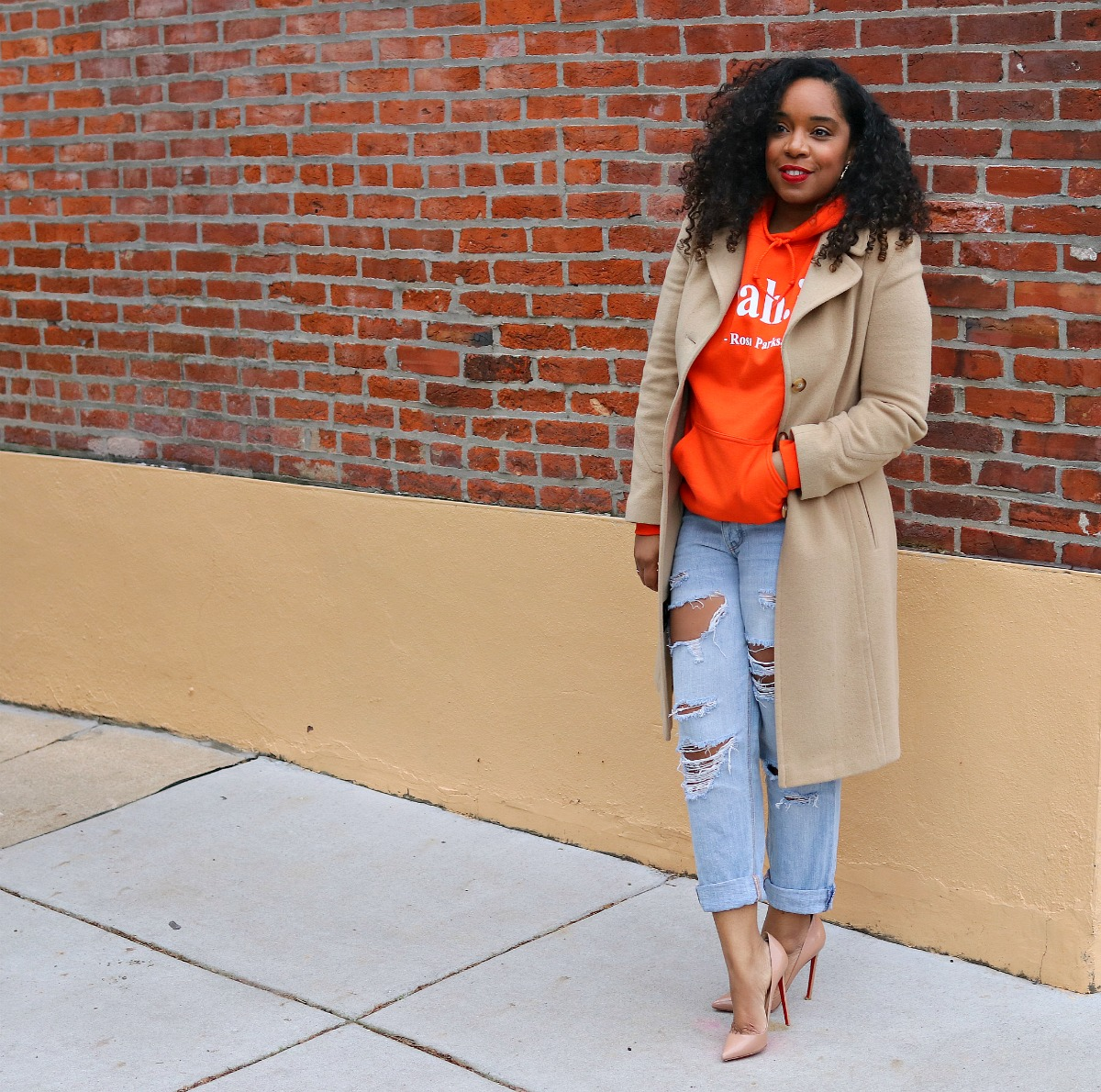 Orange hoodie, nude pumps, camel coat