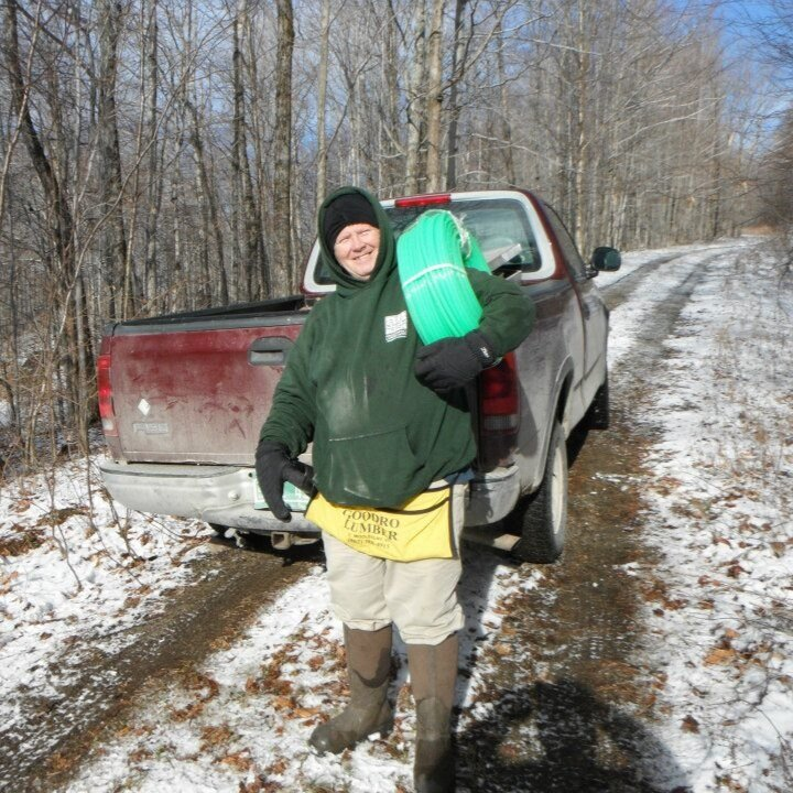 Glynn Simpler, family friend and right-hand-man, heading into the sugar bush with a bundle of line