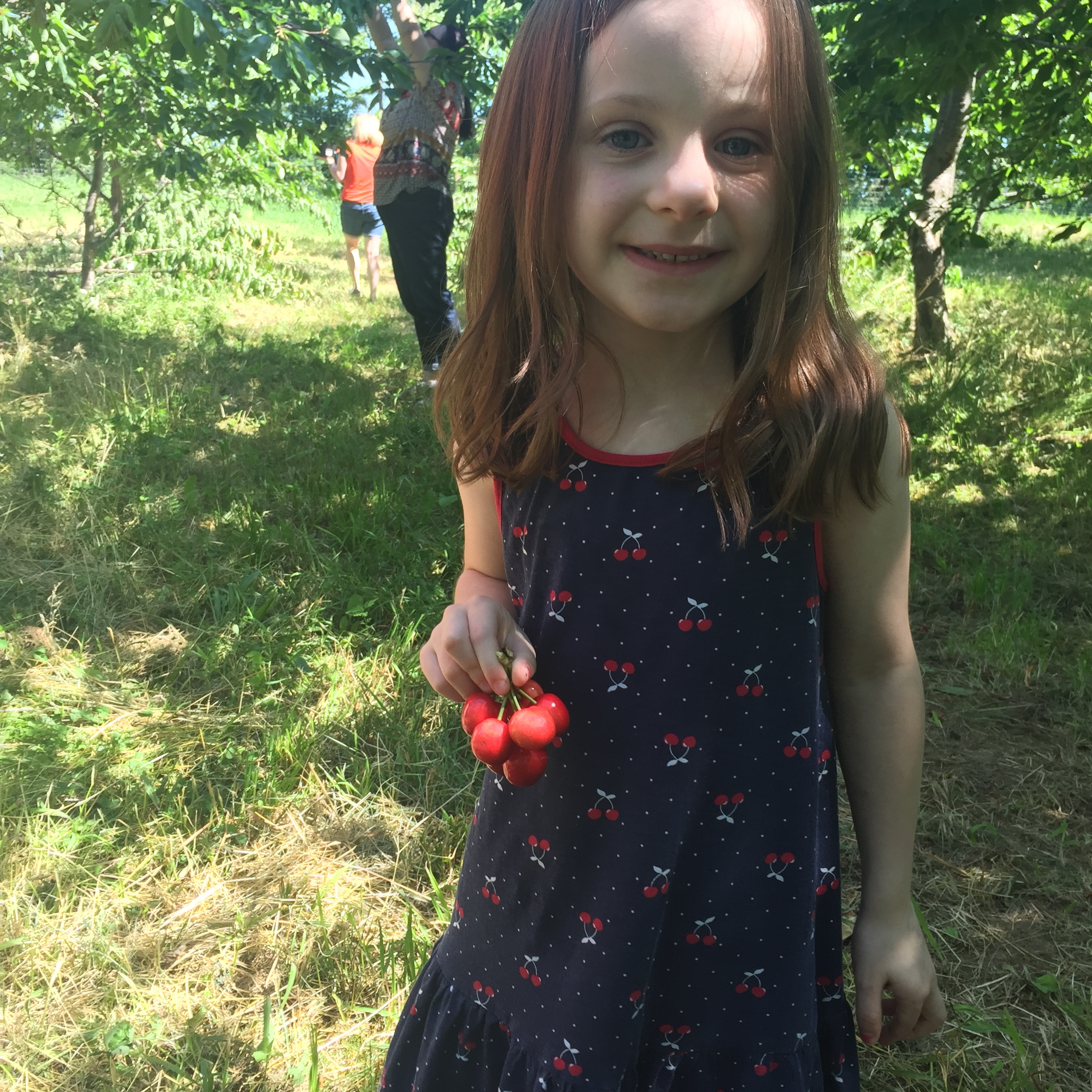 A happy customer with a matching cherry dress