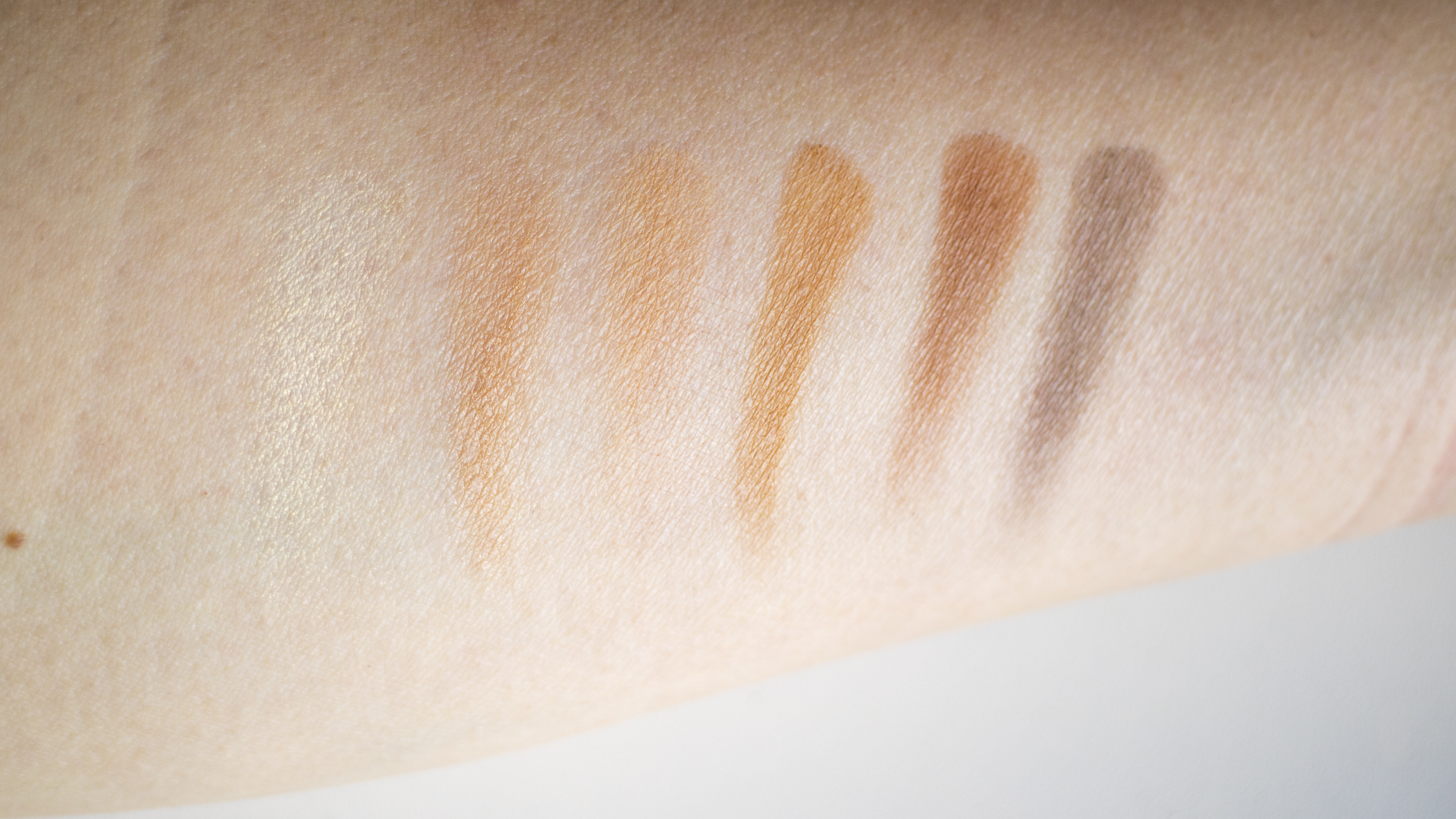 The Legacy Palette Eyeshadow Swatches Top Row (From L to R): Iced Gold, Champagne, Wheat, Camel, Coco, Dark Chocolate