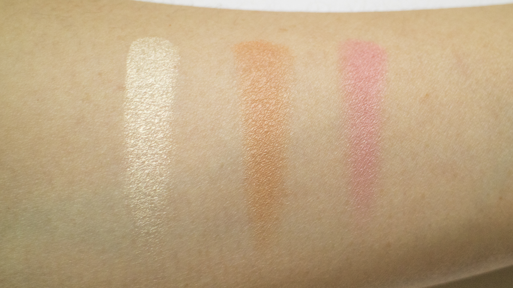 Blushes swatched onto bare arm with brush.