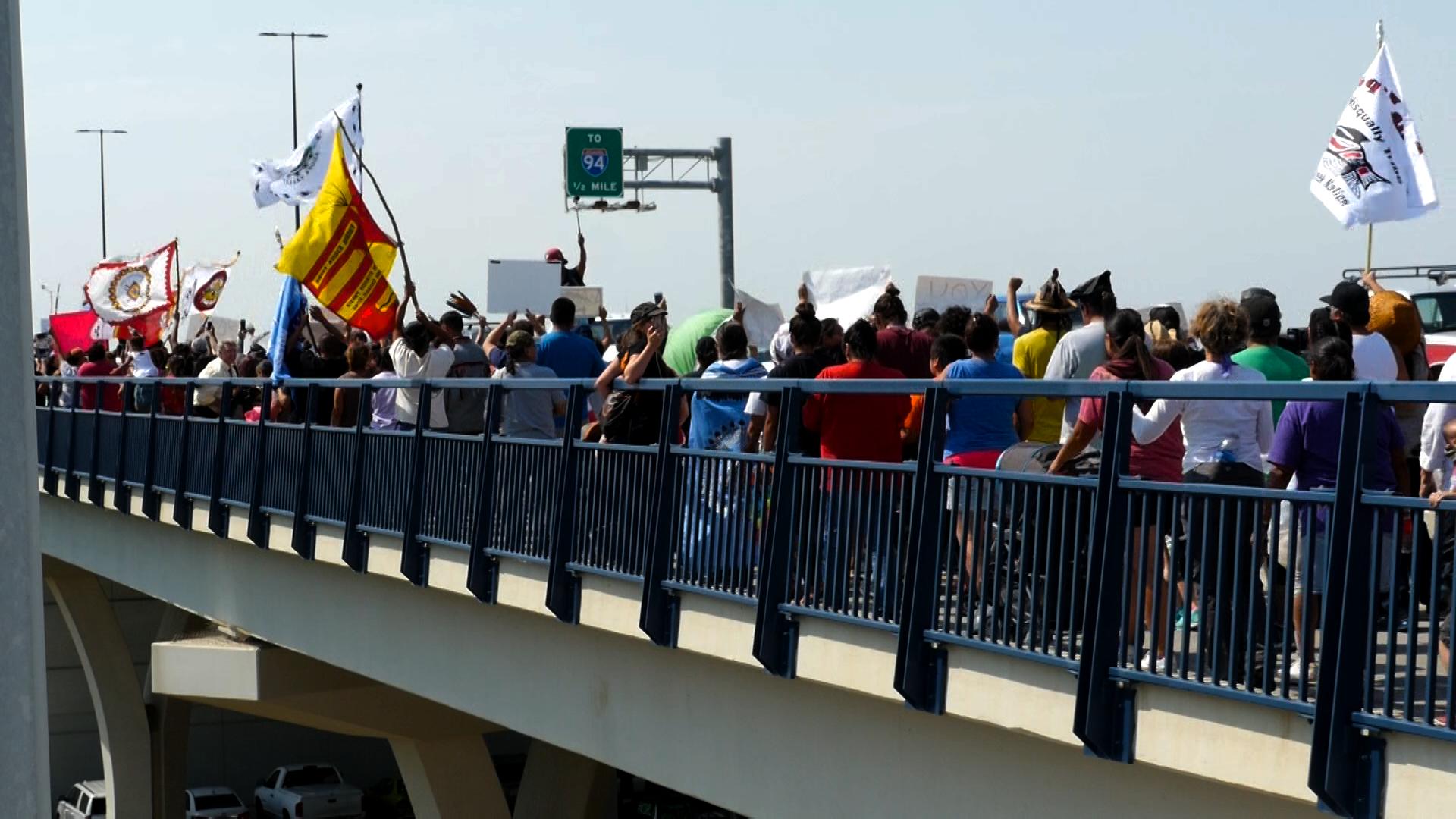 Protestors on the pedestrian path crossing the Memorial Bridge in Bismarck, ND.Photo by Mike Glatt.