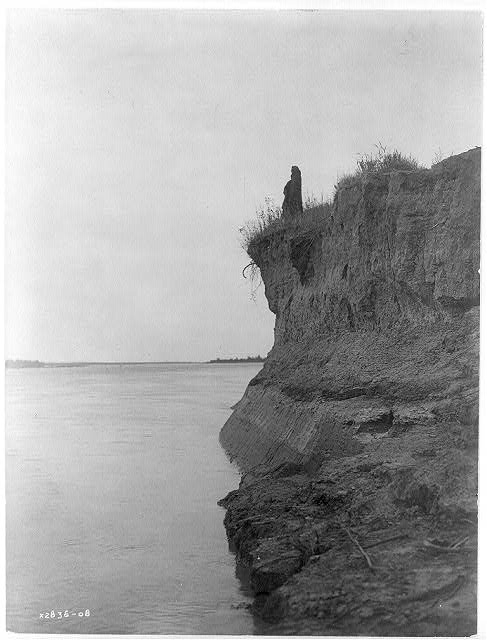 """Photograph by Edward S. Curtis, c. 1908. """"Mandan man wrapped in buffalo robe standing on cliff overlooking the Missouri River."""" From  Wikimedia Commons ."""