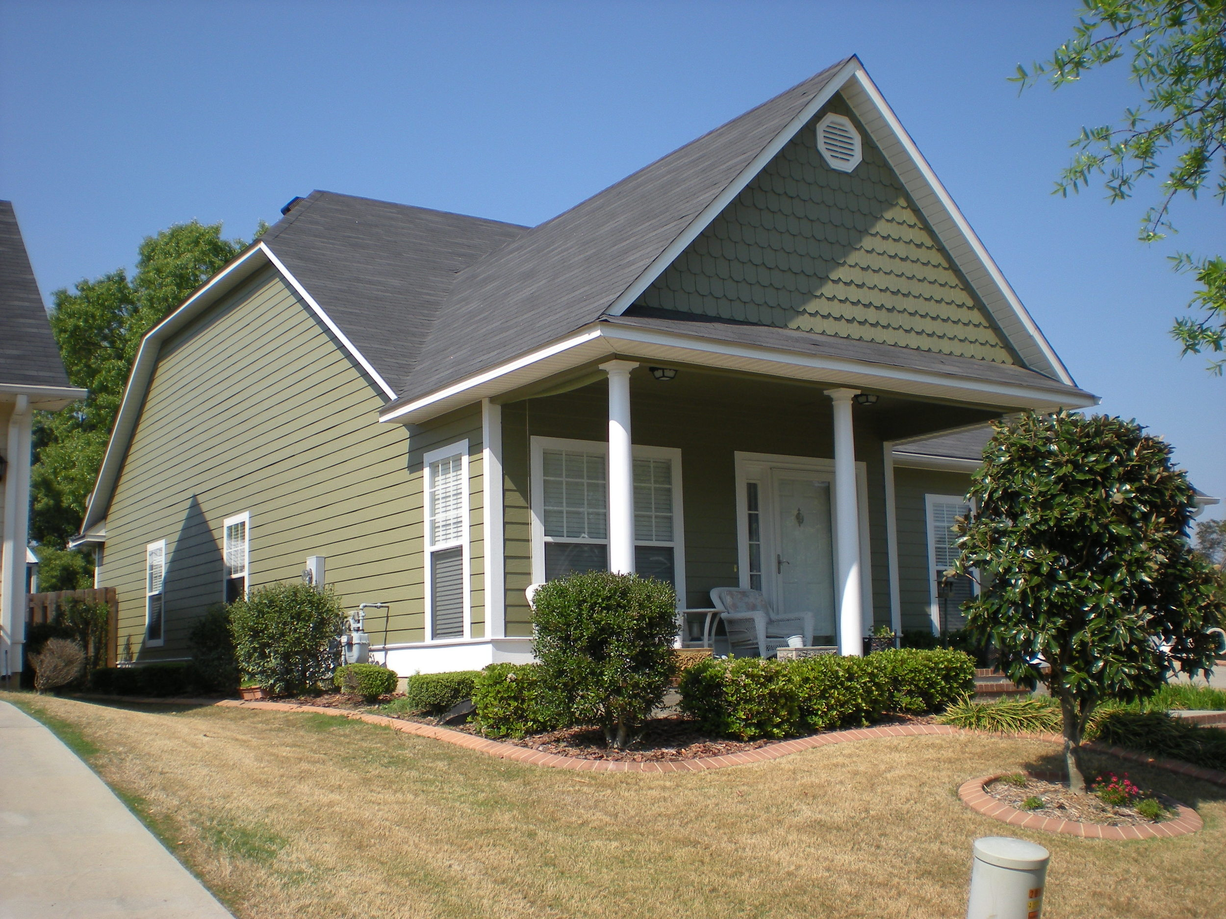 Exterior painting project of siding, trim, garage door, and shed.