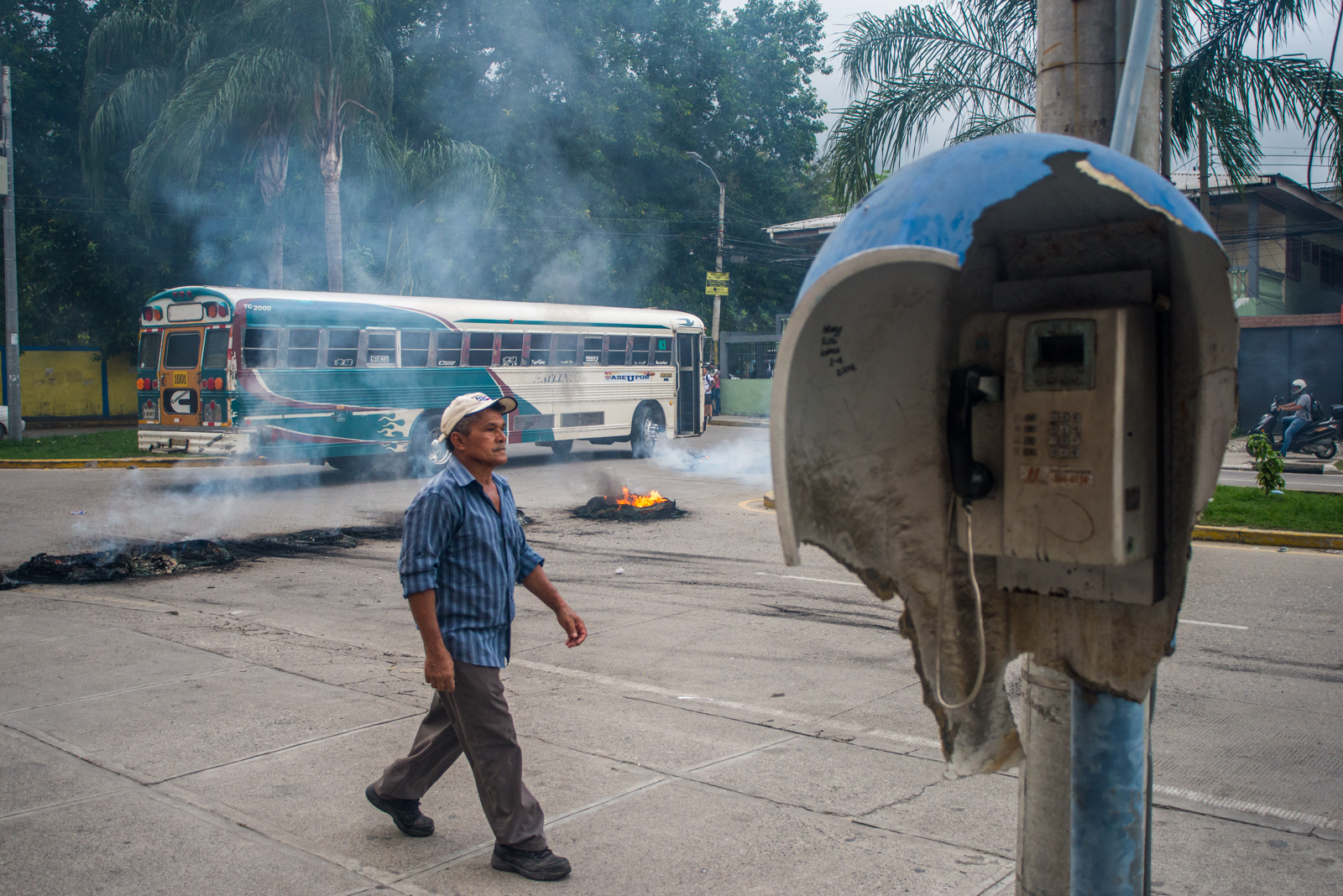 """The remnants of a protest--burnt tires--remain in the street hours after the chaos. This particular protest was due to a rise in public transit tickets. Ironically, a public bus, called """"Rutas"""", is passing by. In Honduras this is a common sight and the passersby continue their life's unaffected."""