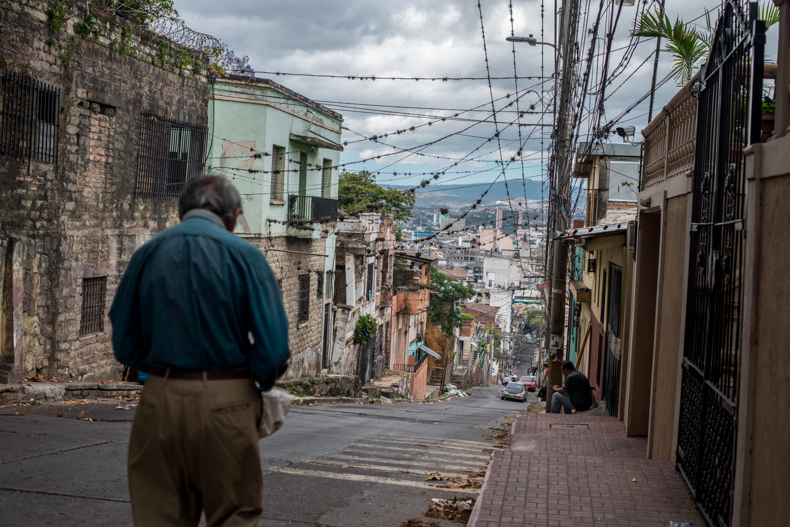 An old man walks down a steep road in one of the poorest barrios,  Buenos Aires, in the capital city of Tegucigalpa.