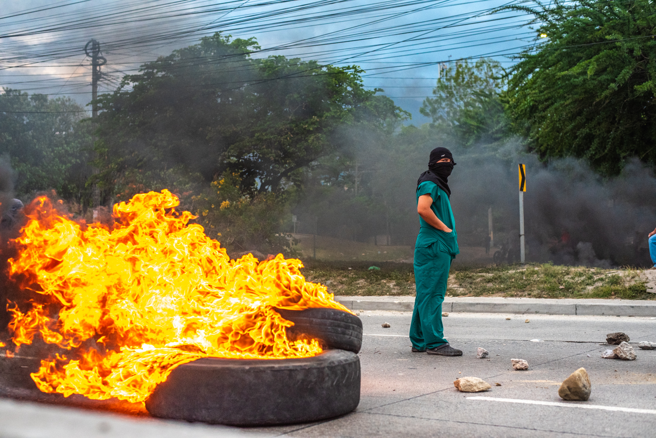 A pharmacy student stands in protest in front of a roadblock in San Pedro Sula.
