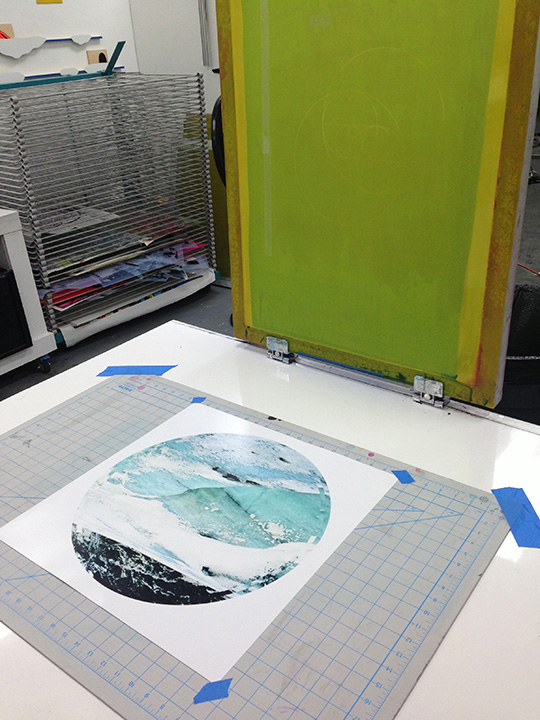 The screen attached to clamps on the table swings down to cover the photo and print ink.