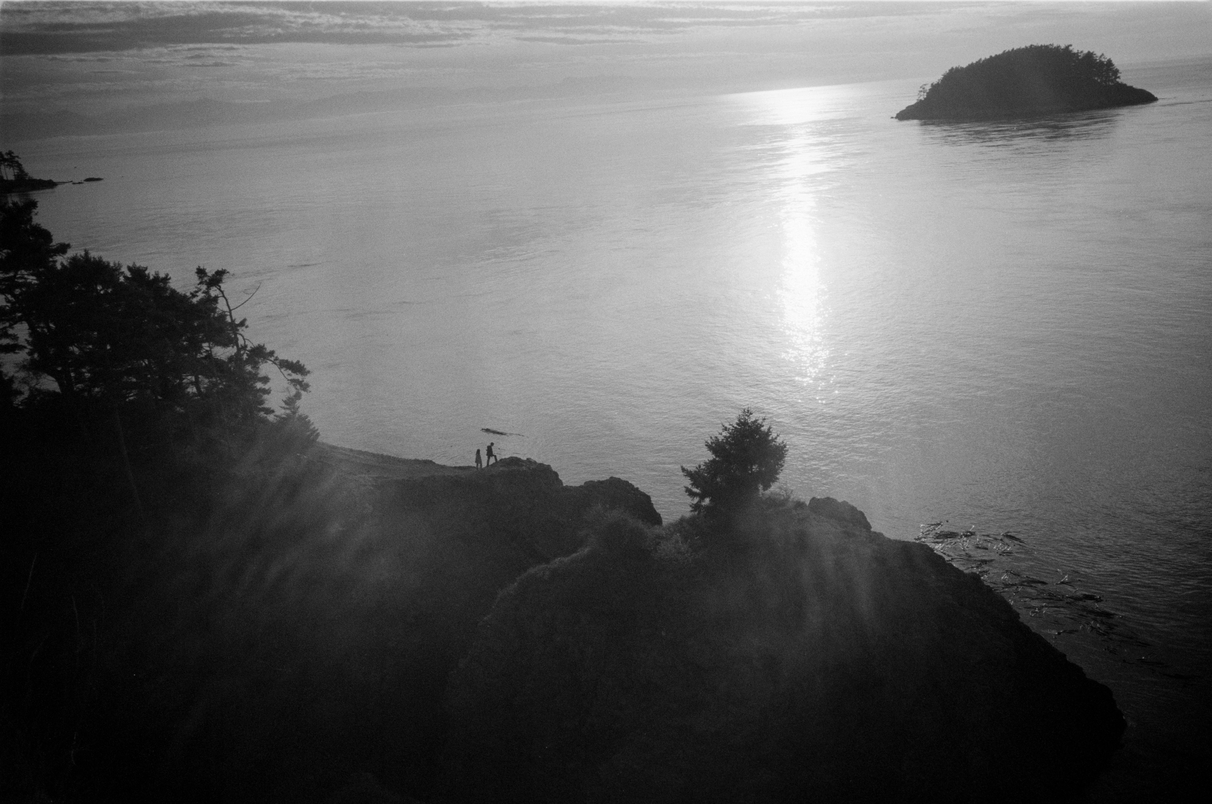 A couple hiking on the Rosario Beach side of Deception Pass.  Whidbey Island, WA.