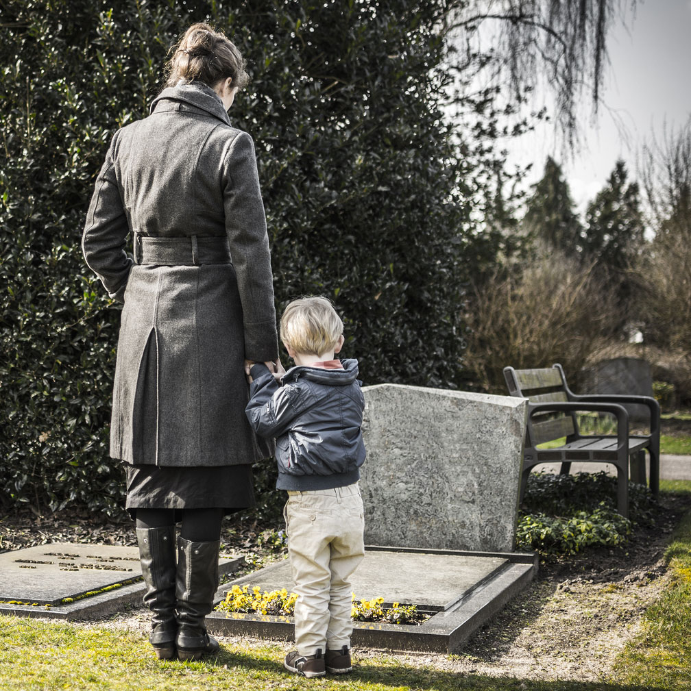 A family grieving at a graveside