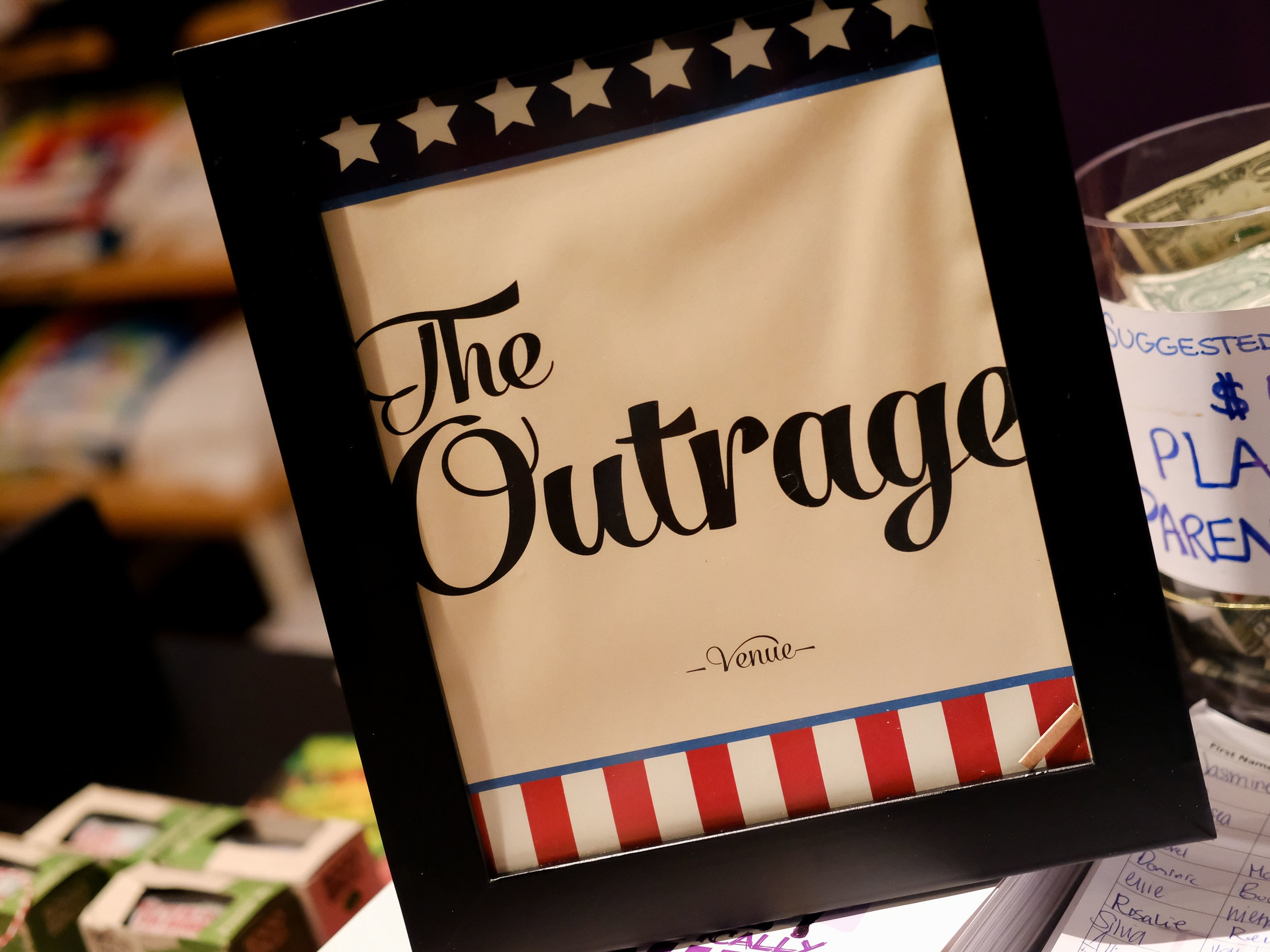 """District Bliss Event Photo, """"The Outrage"""" Venue sign"""