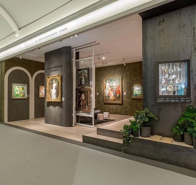 Philip Mould & Company at Masterpiece Fair 2019  This stand as a raw and earthy background to some of the finest paintings. The warmth of the green textured walls made the vibrant colours of the paintings pop. The industrial steel wall to the right of the space housed a steel cabinet for the miniatures, boasting many perfect imperfections in the steel's surface. Looking through the cabinet of the miniature portraits, the viewer can see another interesting segment of the interior - an elevated stage, with steel cladded steps. The platform area walls are adorned with carbonised wooden slates. All the elements come together seamlessly for a dramatic effect.  #4DProjects #philipmouldgallery #gallery #painting #earthy #raw #steel #masterpiece2019