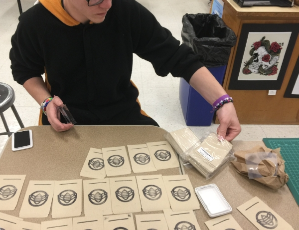 Batavia High School design student prepares new seed packet logo and custom stamp for the Lucy Flower Children's Garden Club.